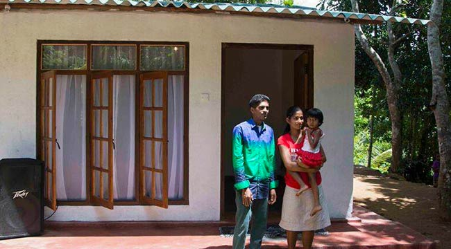 A Family with Their New House Built by Staff of Mahaweli Reach Hotel